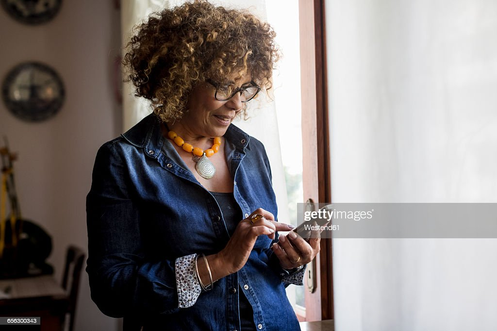 Woman using phablet by the window : Stockfoto