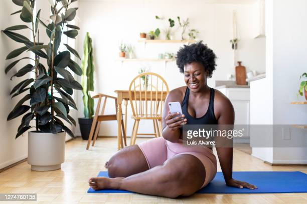 woman using phone after exercising at home - wellness stock pictures, royalty-free photos & images