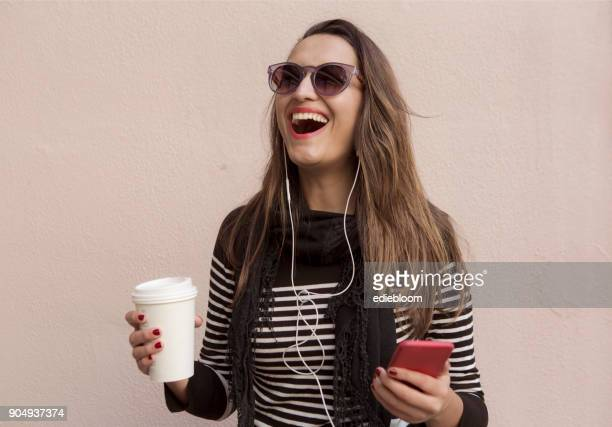 Woman using phone and drinking coffee