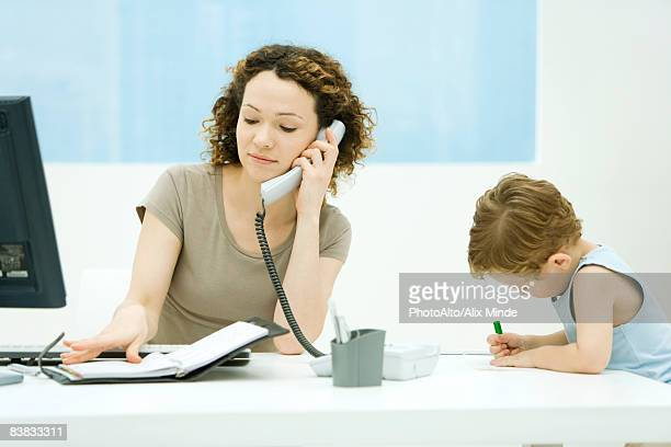 Woman using phone and looking at agenda, young son sitting beside her, coloring