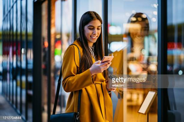 woman using phone and window shopping - phone message stock pictures, royalty-free photos & images