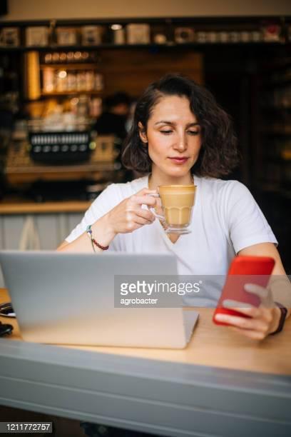 femme utilisant le téléphone au café - finance et économie photos et images de collection
