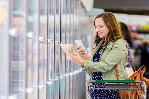 Woman using phone at grocery store - gettyimageskorea