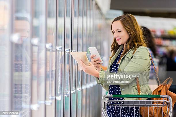 woman using phone at grocery store - contact list stock photos and pictures