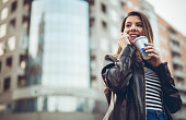 young woman drinking coffee using mobile