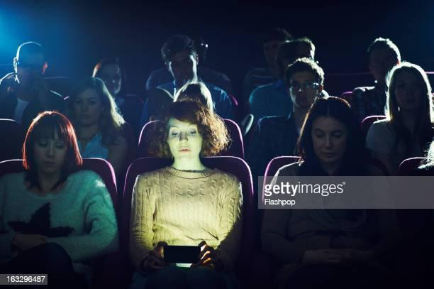 Woman using phone during movie at cinema