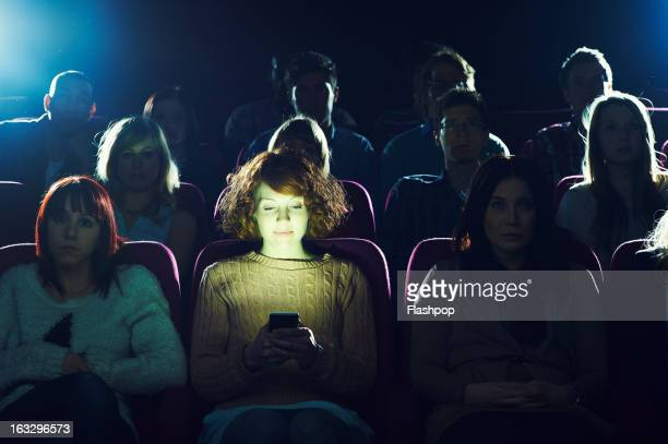 woman using phone during movie at cinema - industrie du cinéma photos et images de collection