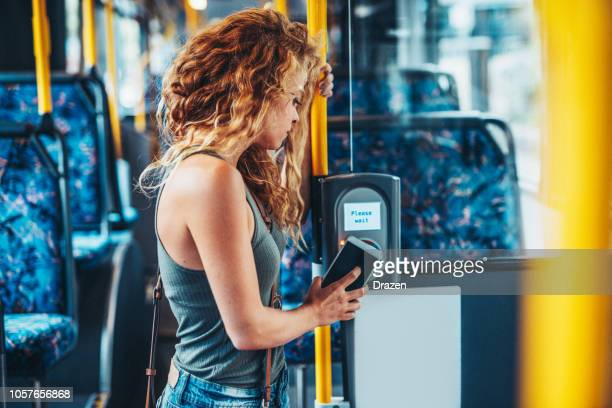 woman using phone for contactless payment on the bus - public transport stock pictures, royalty-free photos & images