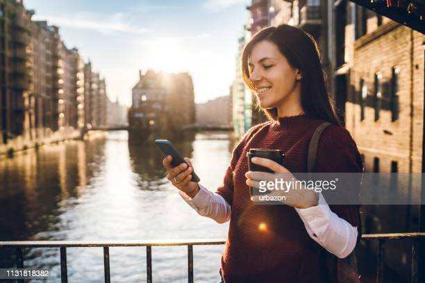woman using phone in hamburg old town - central europe stock photos and pictures