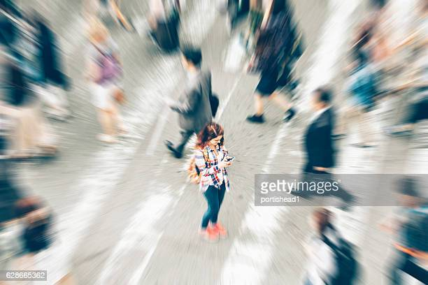 woman using phone in the middle of crowd crossing street - individuality stock photos and pictures