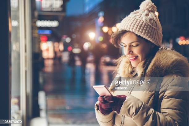 Woman using phone in the winter