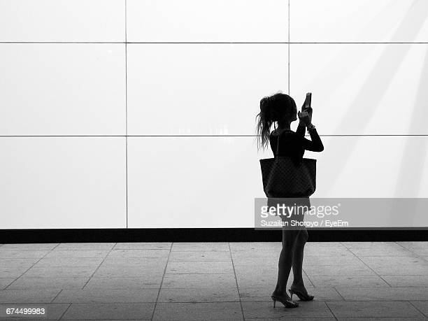 woman using phone on footpath against wall - touch sensitive stock pictures, royalty-free photos & images