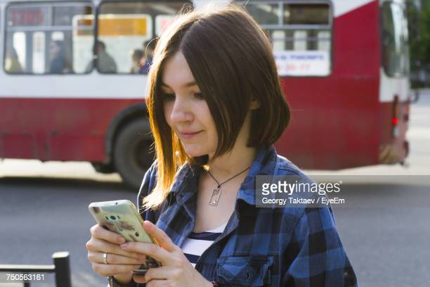 Woman Using Phone On Road Against Bus