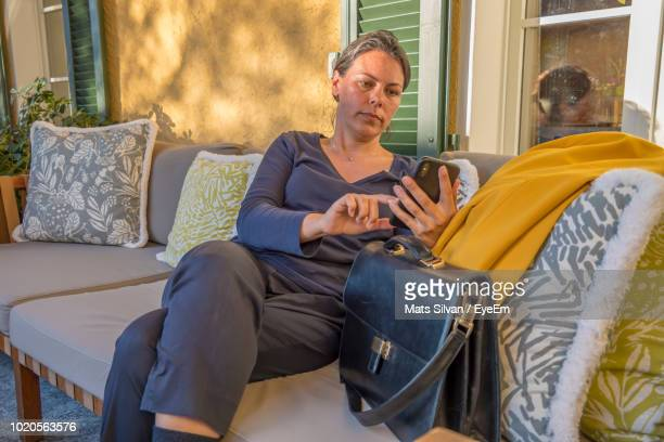 Woman Using Phone On Sofa At Home