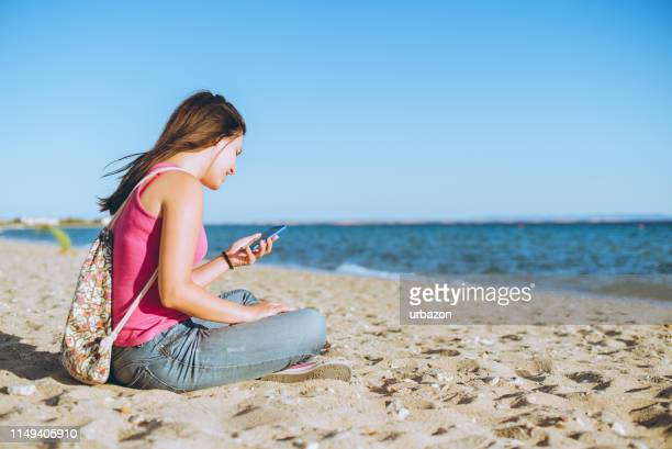 woman using phone on the beach - phone message stock pictures, royalty-free photos & images