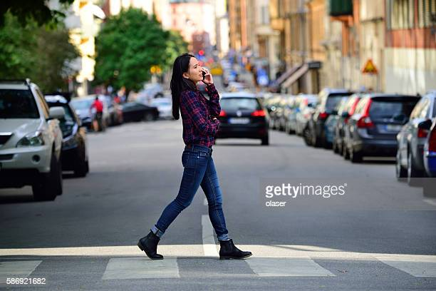 woman using phone stockholm city street in background - pedestrian crossing stock photos and pictures