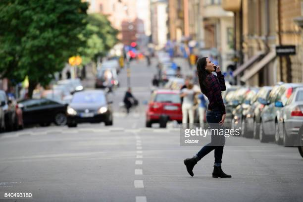 Woman using phone, Stockholm city street in background