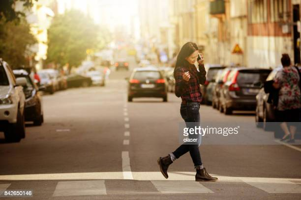 woman using phone, stockholm city street in background - stockholm stock pictures, royalty-free photos & images