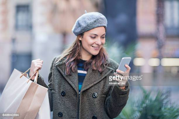 Woman using phone while carrying shopping bags