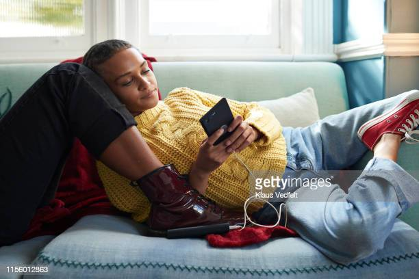 Woman using phone while leaning on friend's leg