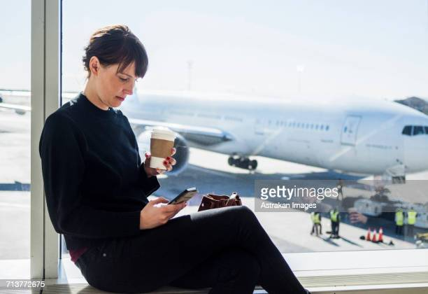 Woman using phone while sitting at airport