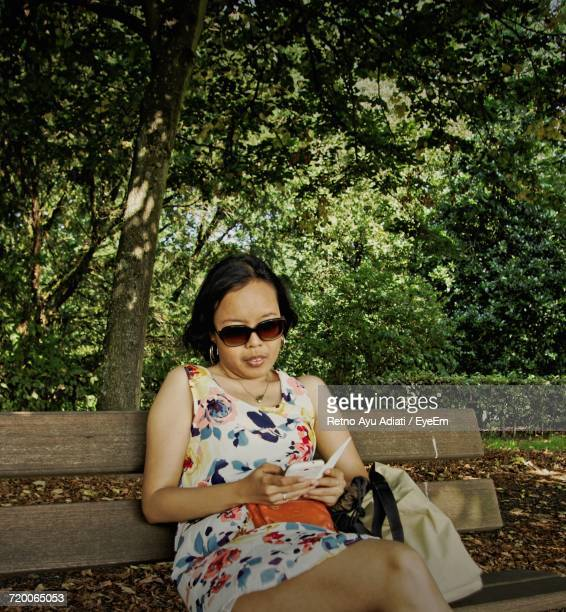 Woman Using Phone While Sitting On Bench Against Trees At Park