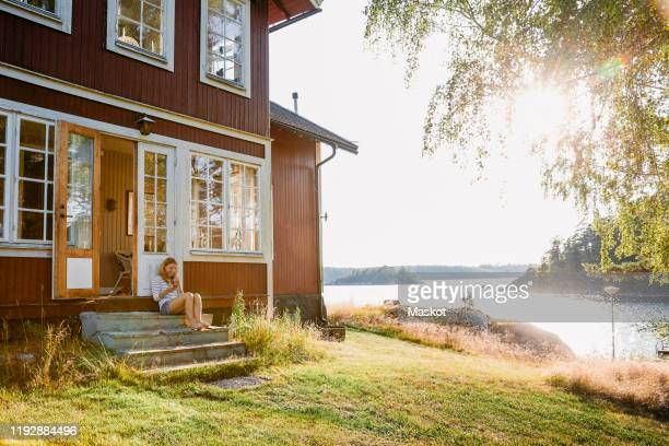 woman using phone while sitting on steps in doorway of log cabin - cottage exterior stock pictures, royalty-free photos & images