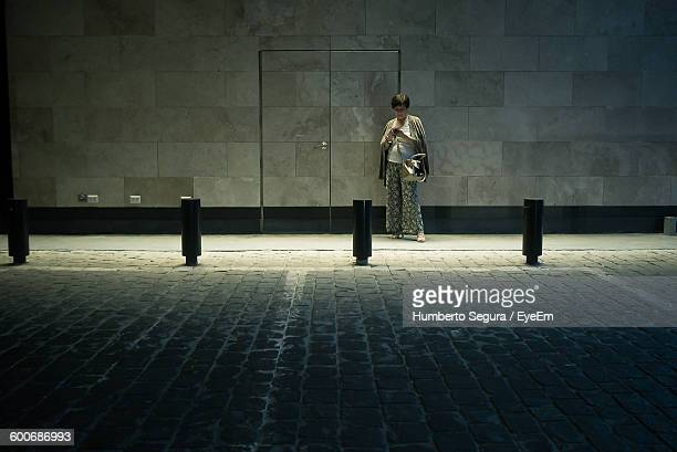 Woman Using Phone While Standing At Sidewalk Against Wall