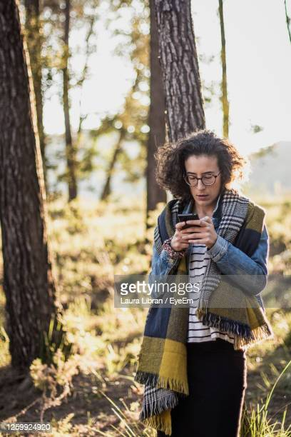 woman using phone while standing in forest - laura woods stock pictures, royalty-free photos & images