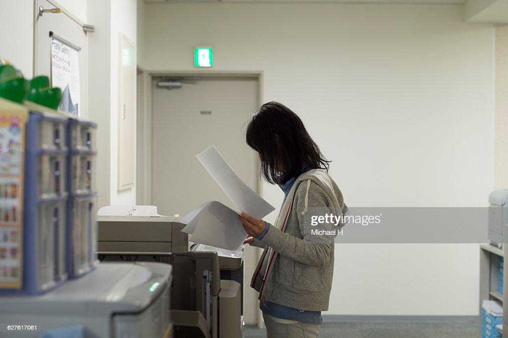 Woman using photocopier : Stock Photo