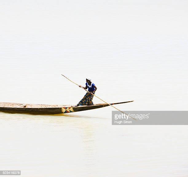 woman using pole to steer canoe in mopti harbor - hugh sitton stock-fotos und bilder