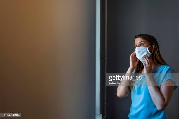 woman using protective mask not to infect her family - nurse mask stock pictures, royalty-free photos & images