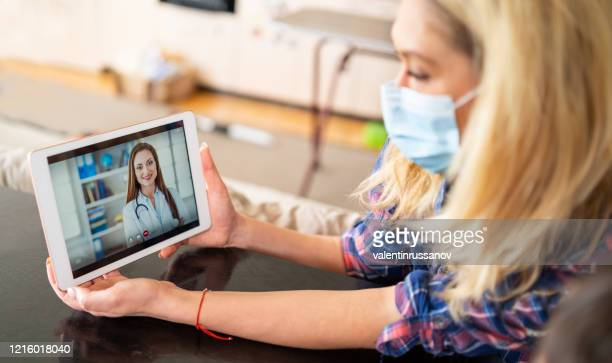 woman using protective mask talking with doctor on laptop isolation at home for virus - telemedicine stock pictures, royalty-free photos & images
