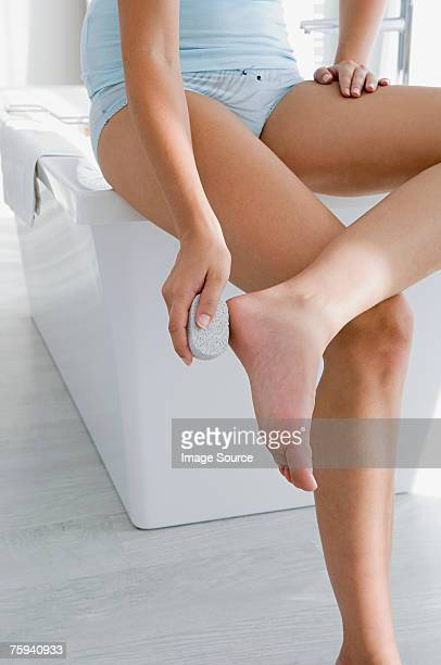 Woman using pumice stone on feet