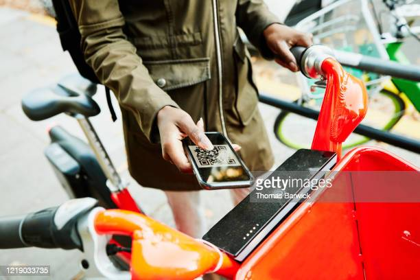 woman using qr code on smart phone to rent bike share bike - sharing economy stock pictures, royalty-free photos & images