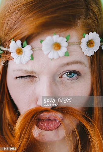 Woman using red hair as mustache.