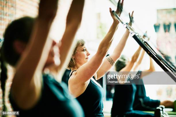 Woman using reformer arm straps during pilates class in fitness studio