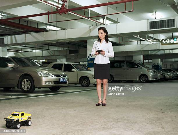 Woman using remote control car in underground car park
