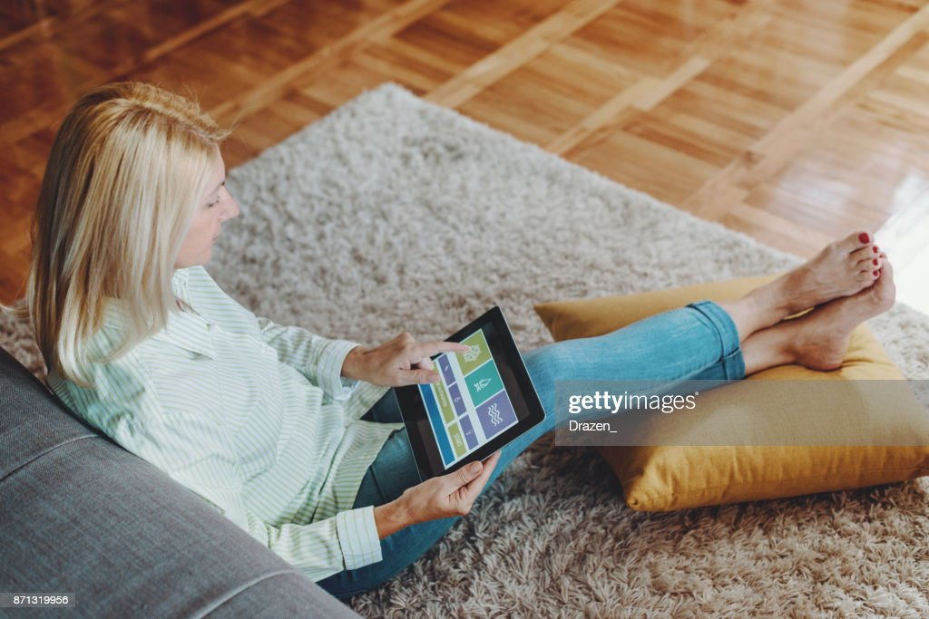 Woman using remote controls of home appliances : Stock Photo