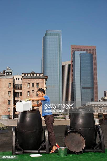 Woman using rooftop compost bin