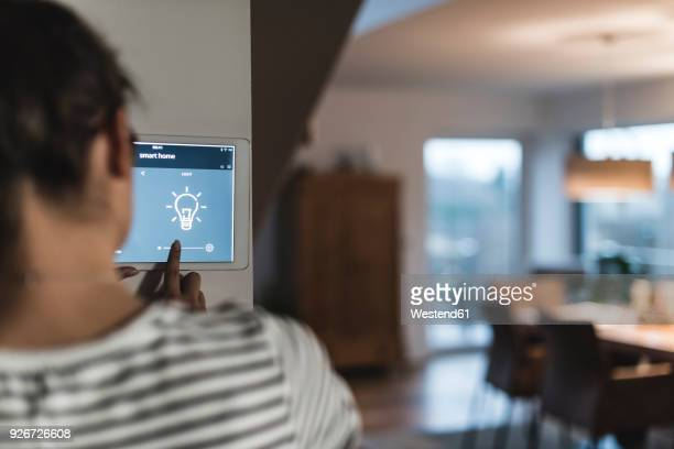 Woman using screen with smart home control functions at home