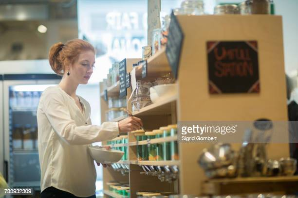 Woman using self service dispensers in shop