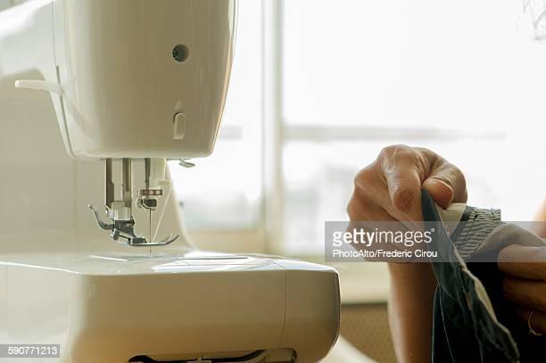 Woman using sewing machine, cropped