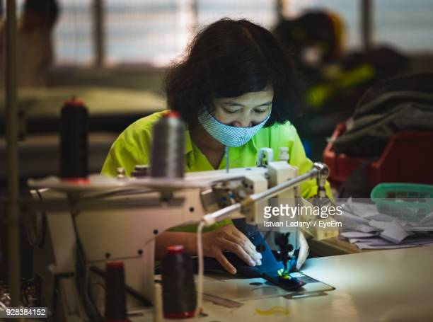 Woman Using Sewing Machine While Working In Factory