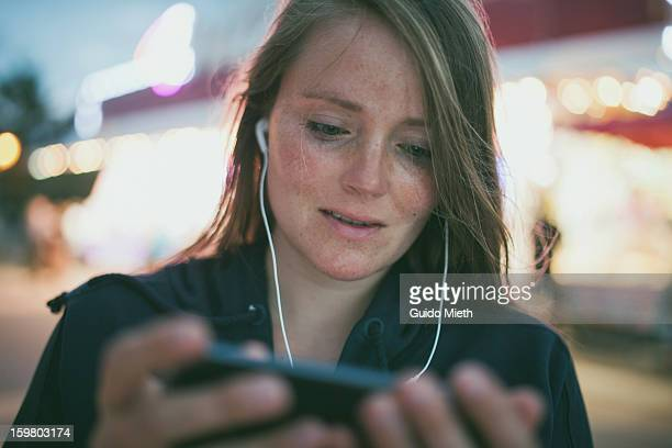 Woman using smart device outdoor.