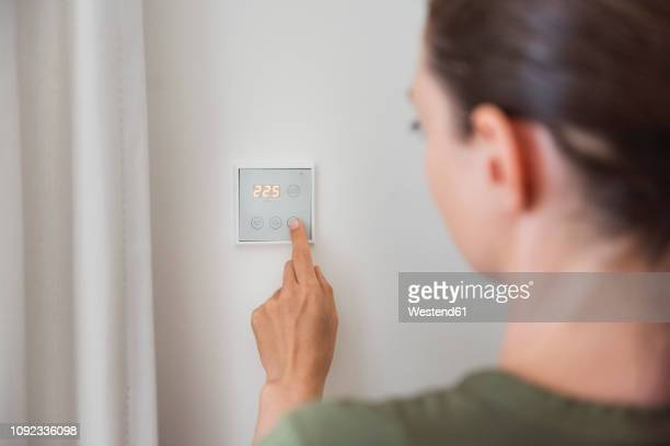 woman using smart home switch on wall - heat stock pictures, royalty-free photos & images