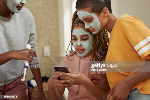 woman using smart phone amidst female friends - vanity stock pictures, royalty-free photos & images