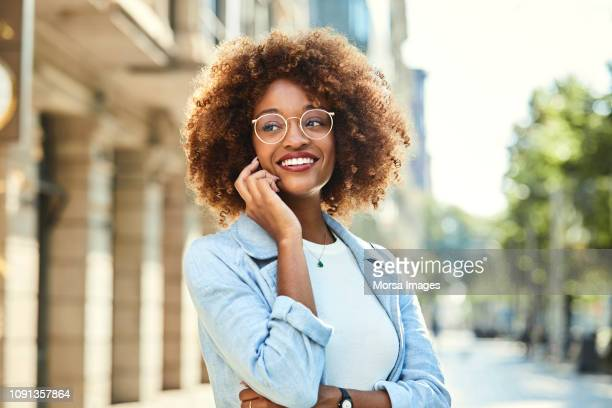 woman using smart phone at sidewalk in city - fashionable stock pictures, royalty-free photos & images