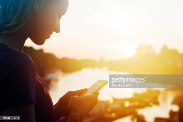 woman using smart phone at sunset - heat haze stock pictures, royalty-free photos & images