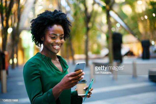 woman using smart phone, holding coffee, smiling - black purse stock pictures, royalty-free photos & images